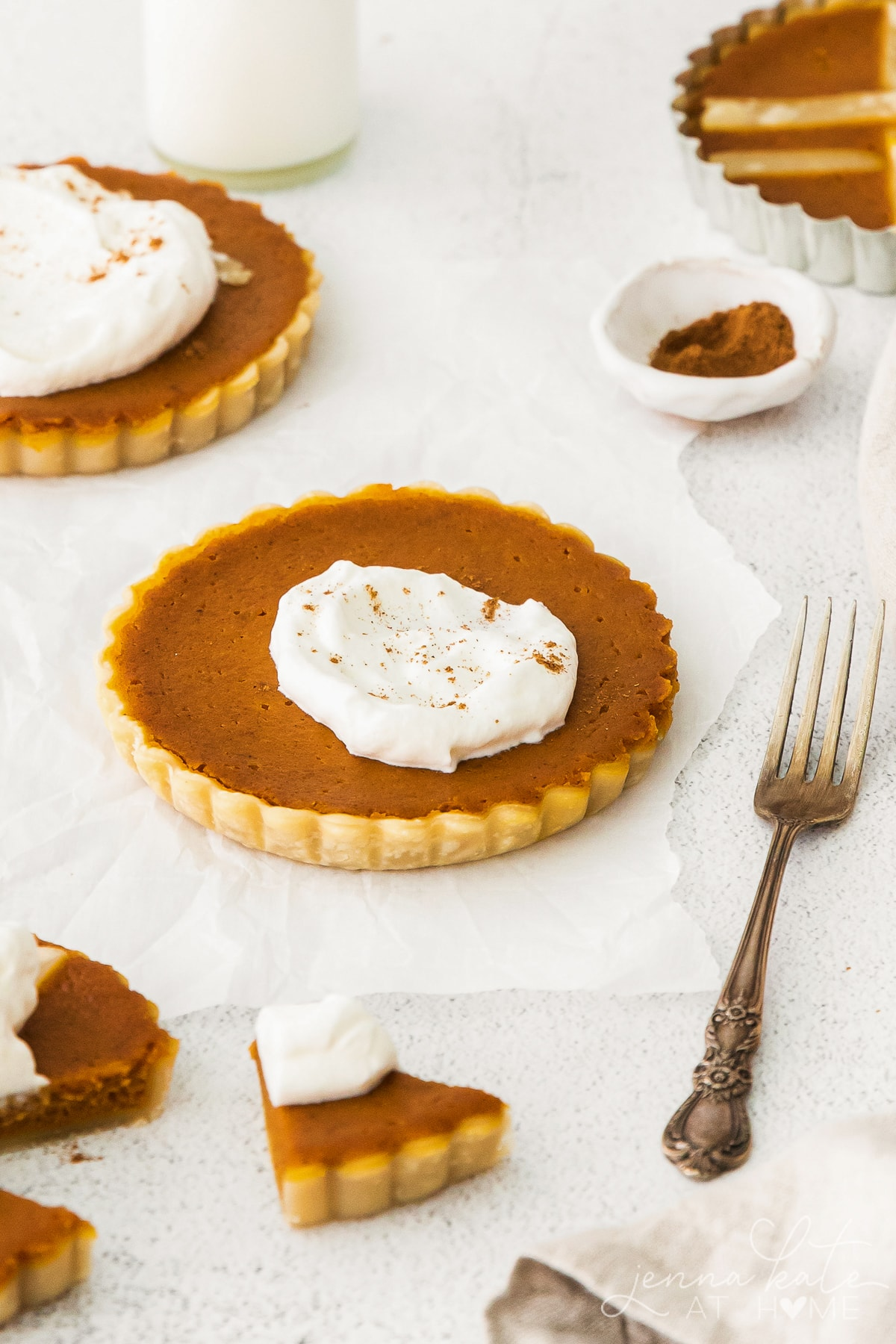 several mini pumpkin pie tarts with whipped cream on top