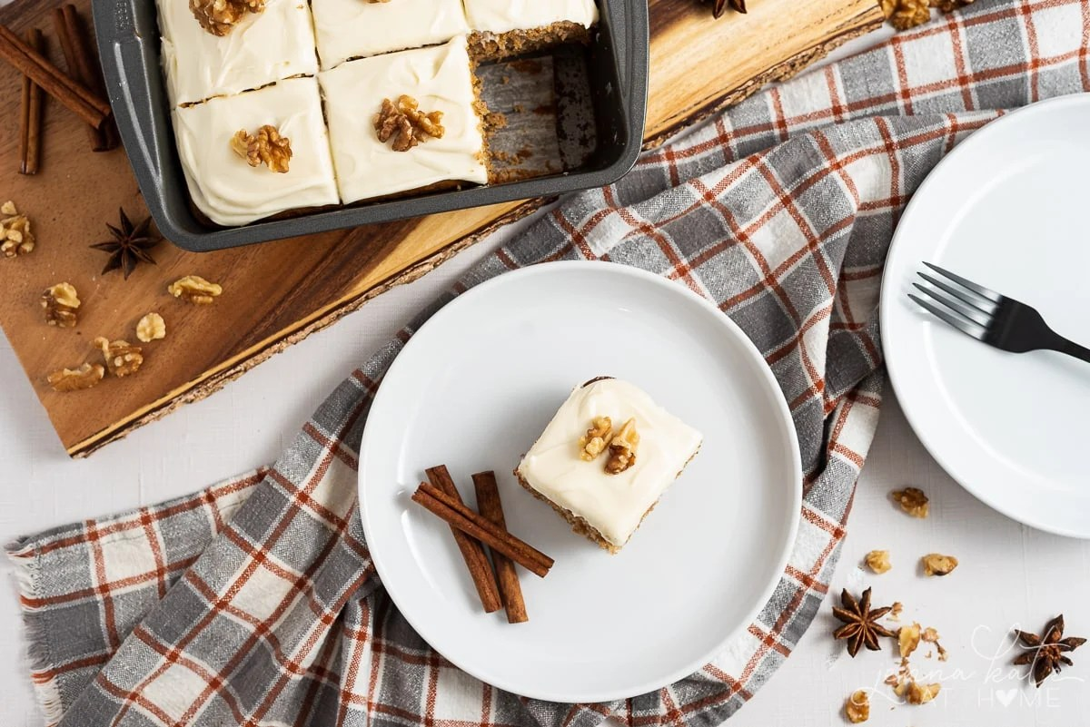 slice of old fashioned spice cake on a plate with cinnamon sticks