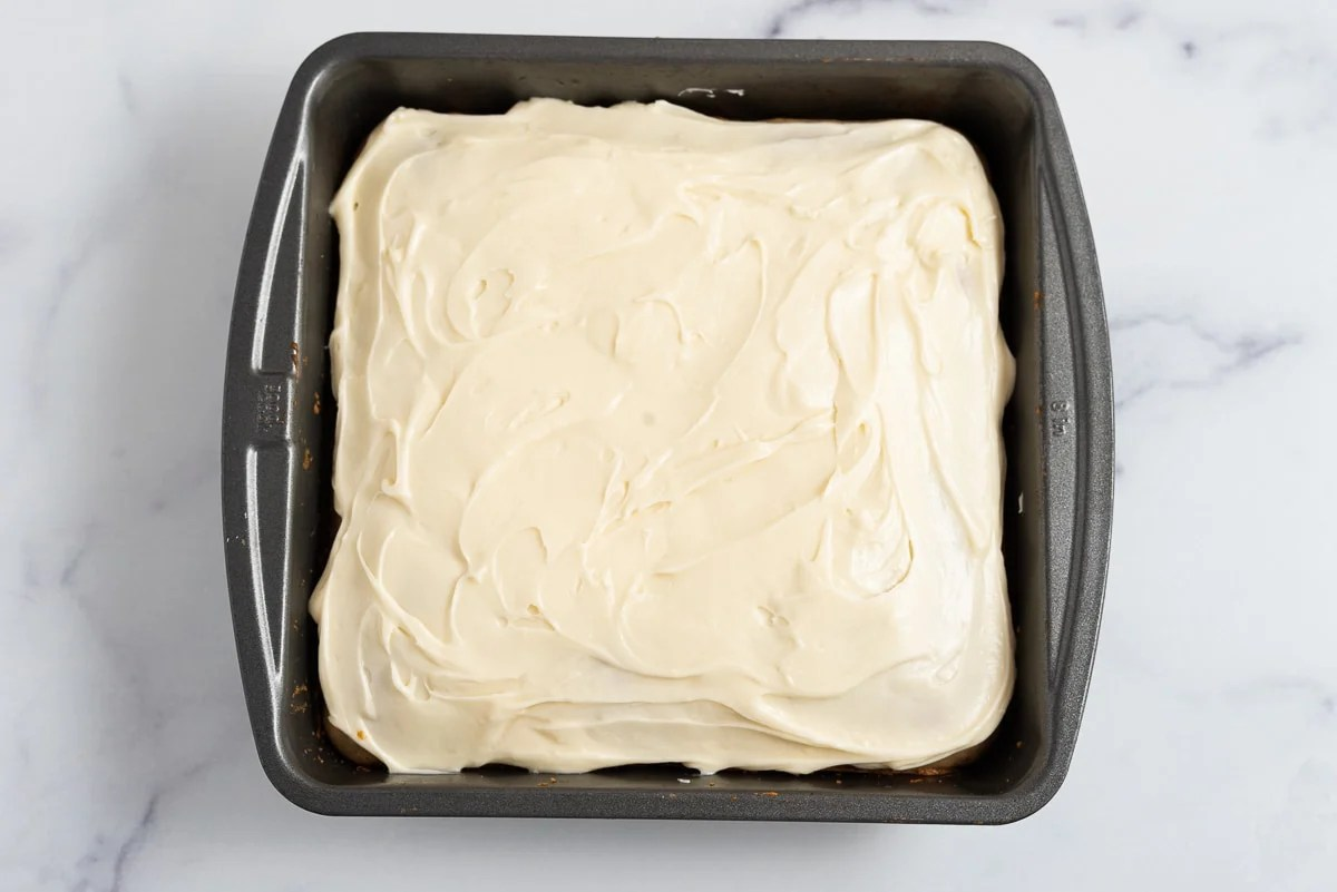 old fashioned spice cake in the pan with cream cheese frosting