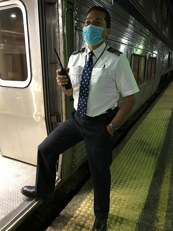 An Amtrak employee in a coronavirus mask waiting for the train to resume.