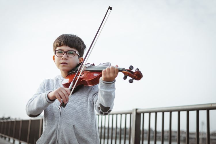 Young boy stands poised to play his violin.
