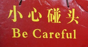 Sign at entrance to a cave. Be careful not to hit your heads on the protruding rocks.