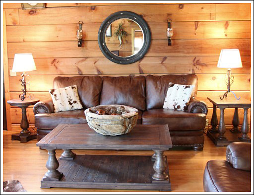 log cabin living room. I added a large black distressed mirror  flanked with candle sconces Two wooden side tables balance out the weight of leather couch Log Cabin Living Room Before and After Photos