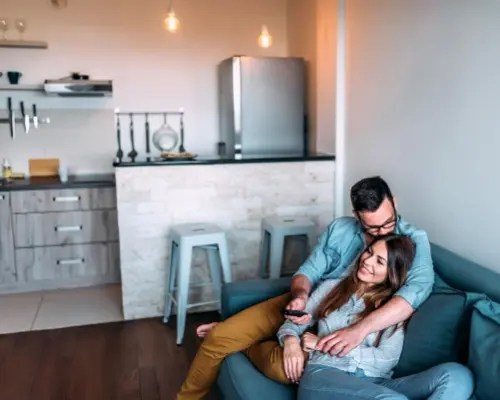 A couple embraces each other on the couch. They are much happier after starting marriage counseling in Dallas Fort Worth with marriage counselor Jennifer Gay through Rethink Therapy.