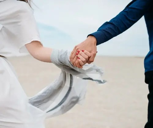 A couple holds hands. They are feeling happy after starting online marriage counseling in Dallas, TX with Rethink Therapy 75205.