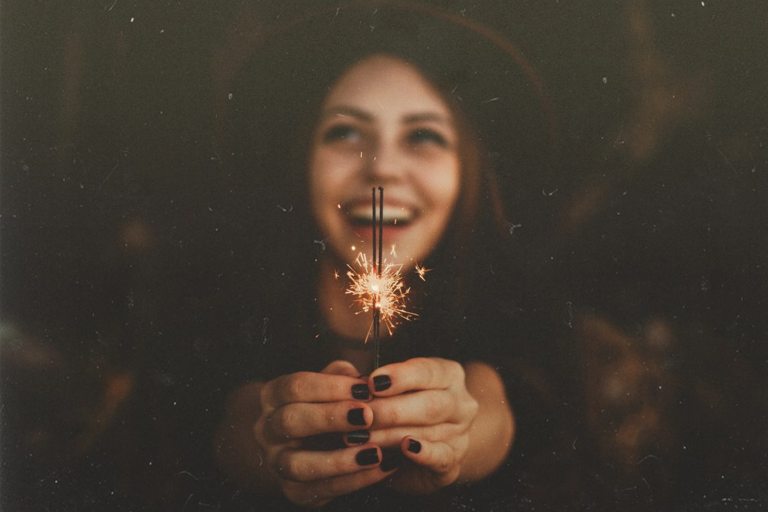 A girl smiles while holding a sparkler. She is feeling happy after starting trauma therapy in Dallas, TX with Rethink Therapy.