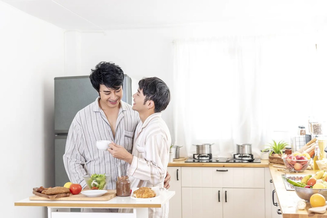 A young male couple stand closely in their kitchen embracing each other. They are feeling much happier since they have started LGBTQ+ counseling in Texas with Rethink Therapy.