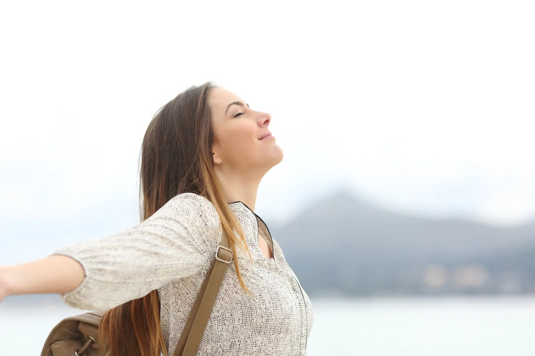 Side view portrait of a happy woman breathing fresh air on the lake feeling free and fresh after trauma therapy in Dallas, TX with Jennifer Gay. EMDR trauma therapist in Dallas, TX can help you with online therapy in Texas.