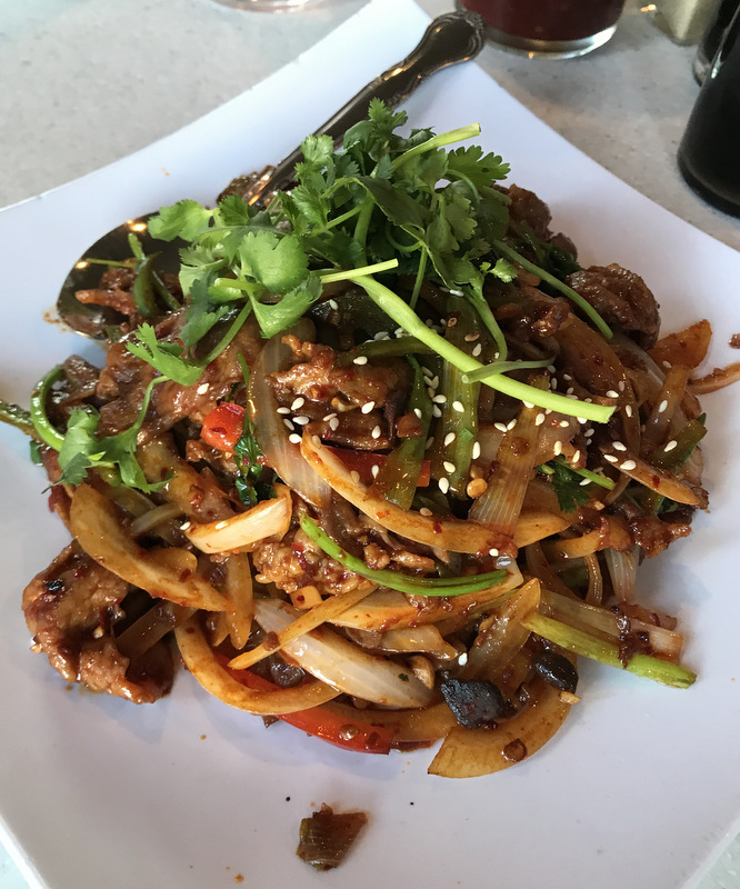 Chinese eggplant with basil and mushrooms, topped with sesame seeds, cilantro, and stir-fried onions