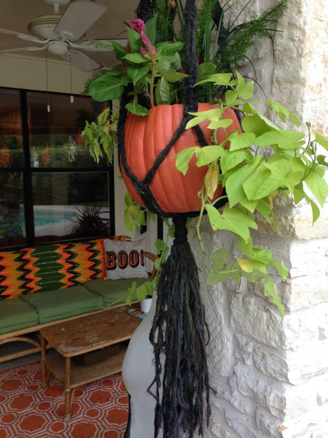 Hanging pumpkin planter on a fall porch