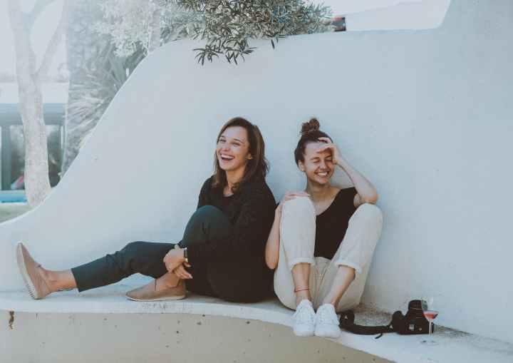 two women sitting on white bench