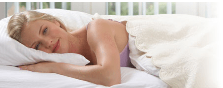 women laying in bed on comfortable pillow with a smile and hand tucked under pillow