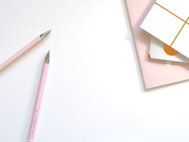A white desk, with pink pens and pink and white notebooks