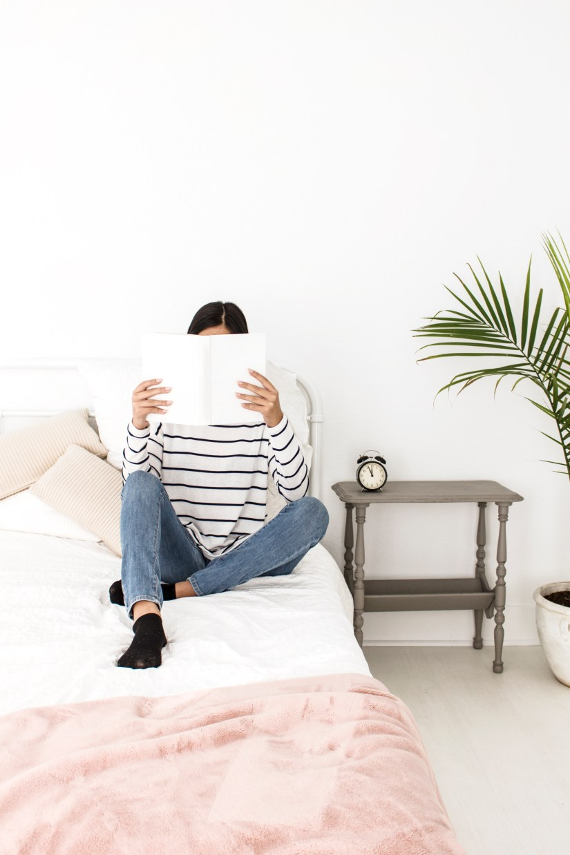Photo for blog post around 10 year goals. A Woman sitting on a bed holding a book in front of her face with a plant and table next to her