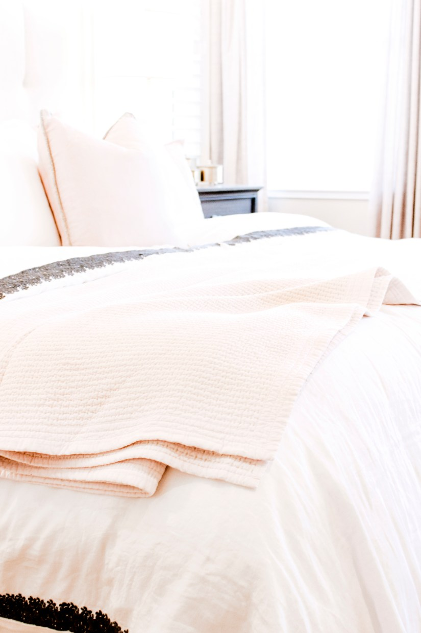 Photo of a made bed with a pink blanket