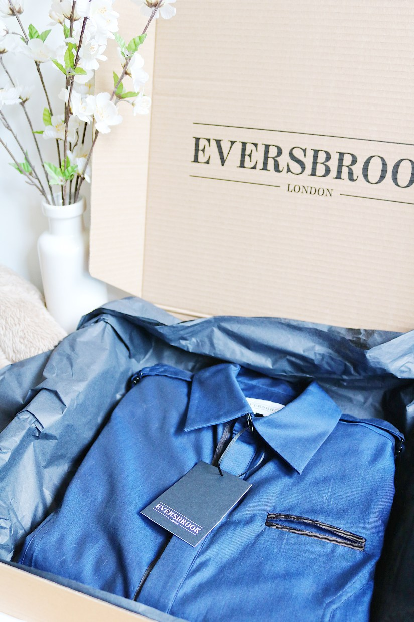Opened box containing a dark blue men's shirt