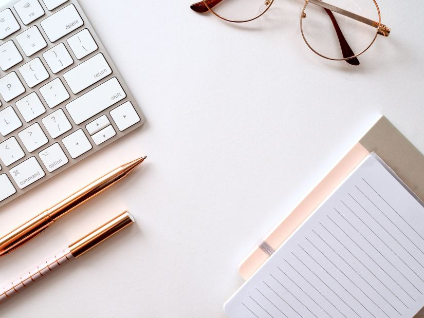 How Much Does Blogging Cost? Flat lay image on a key board, rose gold pens, glasses and a notebook