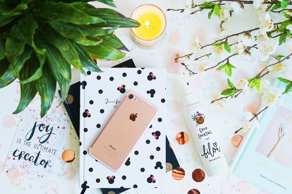 Blogging Pet Peeves: Flat lay consisting of 2 stacked notebooks with an iPhone on top. A candle, a book and flowers