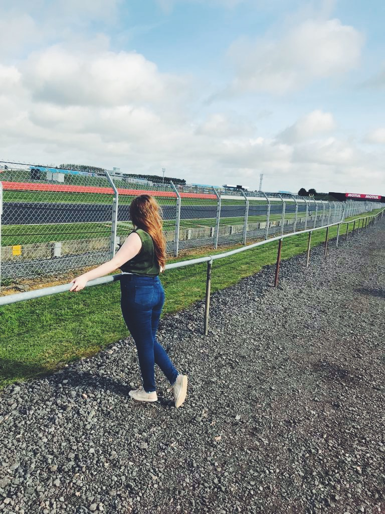A girl at a race track leaning on the barrier facing away from the camera, looking at the circuit. Wearing jeans and a green sleeveless shirt.