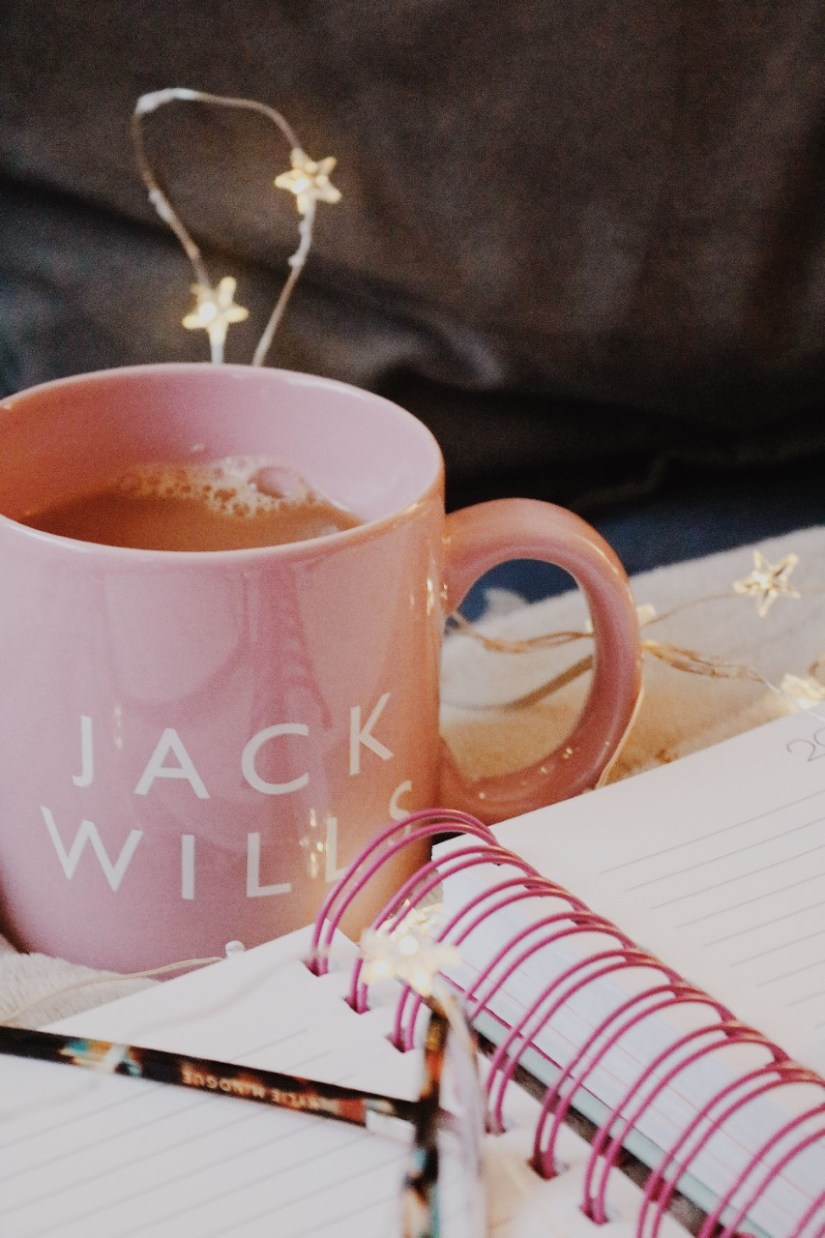 Weekly Blogging Tasks: A cup of tea in a pink Jack Wills mug, with an open notebook in front of it
