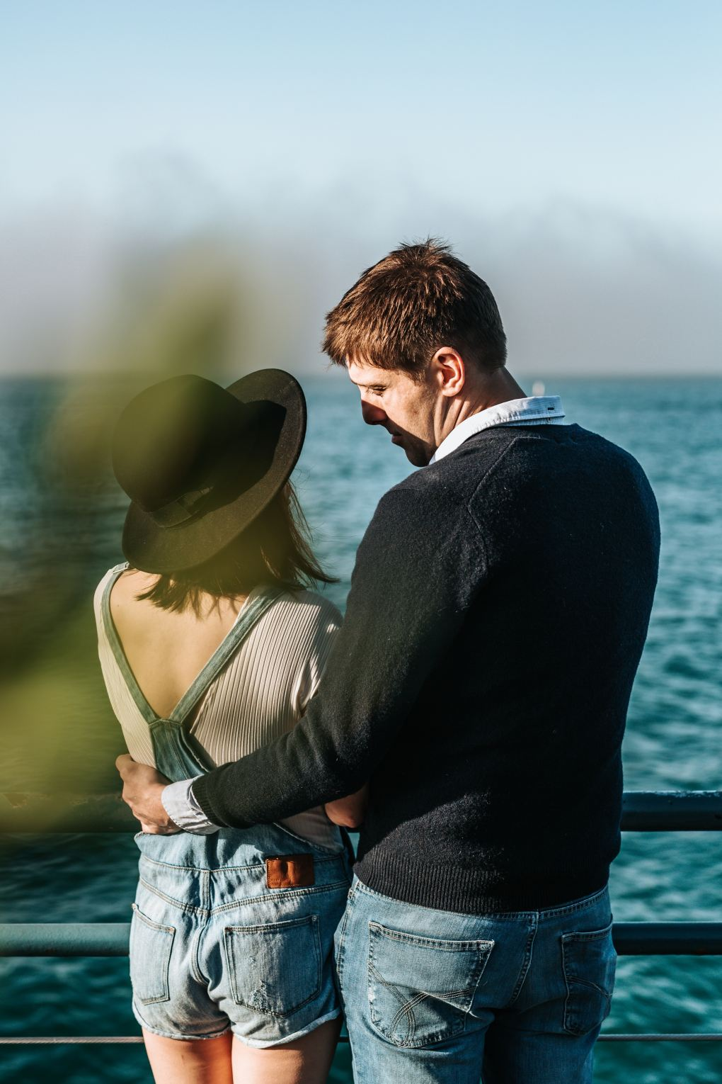 Man wearing a black jumper and woman wearing dungarees and a hat standing by a railing looking out over the sea