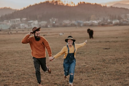 Happy couple running together in a field holding hands
