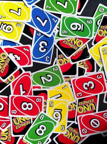 A collection of vibrant Uno cards sits on a black surface.