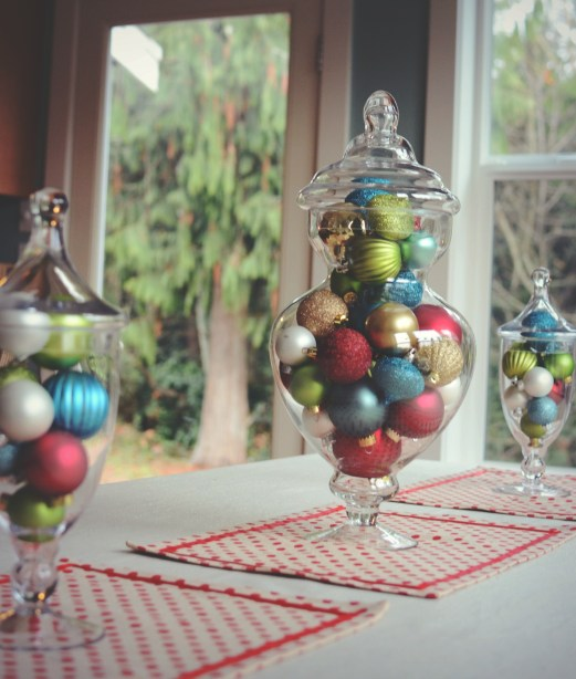 HomeGoods holiday table... Colored ornaments in glass jars by @jennyonthespot