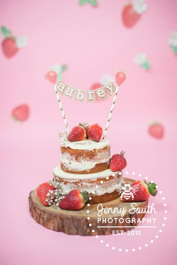 Strawberry naked cake for themed cake smash photography session.