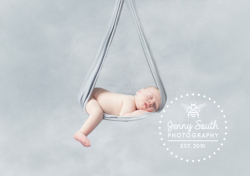 Newborn baby in a grey hammock