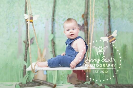 Baby boy on swing in custom made woodland set