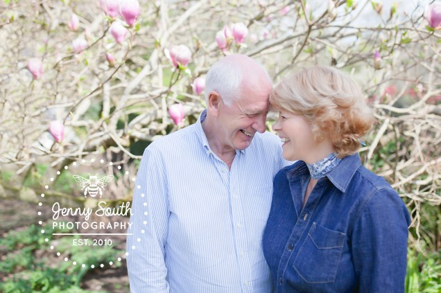Happily married couple in front of blooming magnolia in the Cornish sunshine