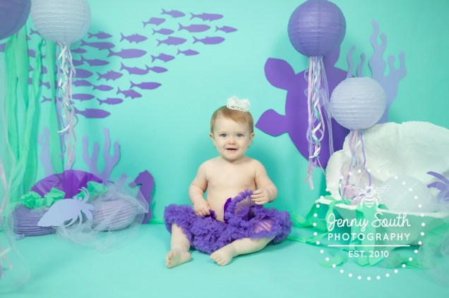 Baby girl turning one dressed in a purple tutu in an underwater themed photography session.