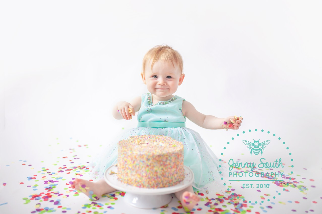 Baby Girl wearing mint coloured dress smashing a confetti cake during a session at Jenny South Photography