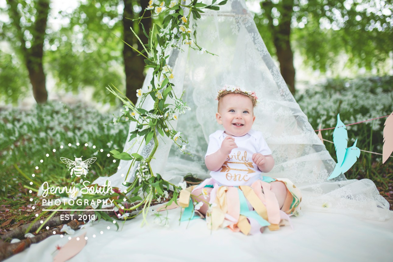 Baby girl celebrating her first birthday in a beautiful lace tee-pee surrounded by wild garlic