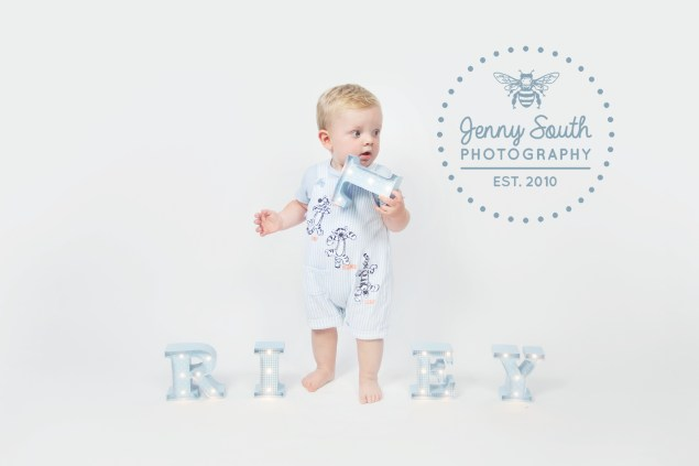 Baby stands in a line with light up letters of his name for a photography session in Plymouth