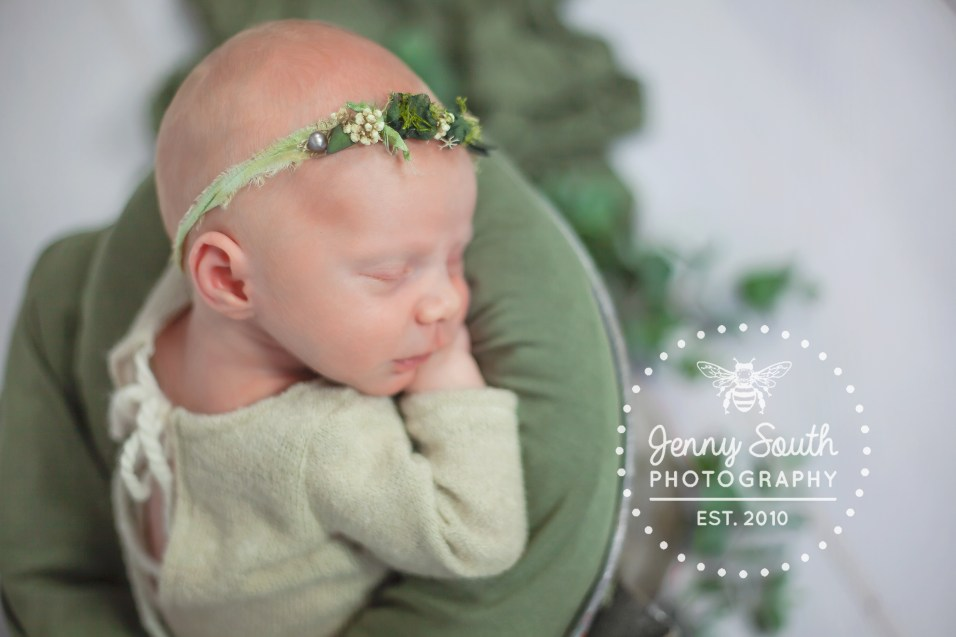 Newborn baby girl sleeps in a bucket with Eucalyptus leaves in the background