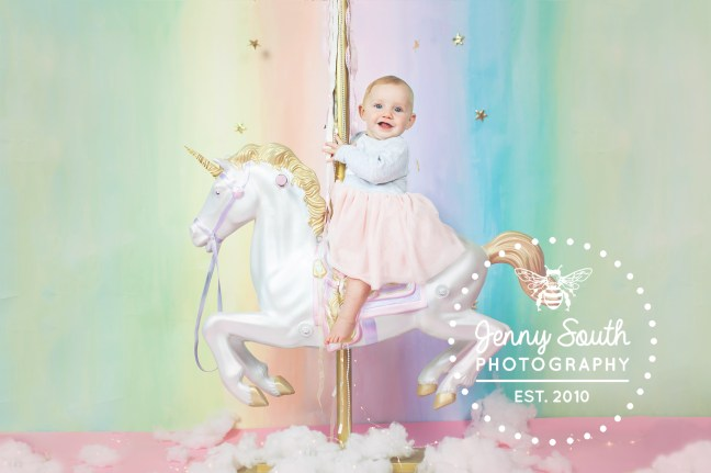 Baby C riding a unicorn against a rainbow backdrop upon clouds