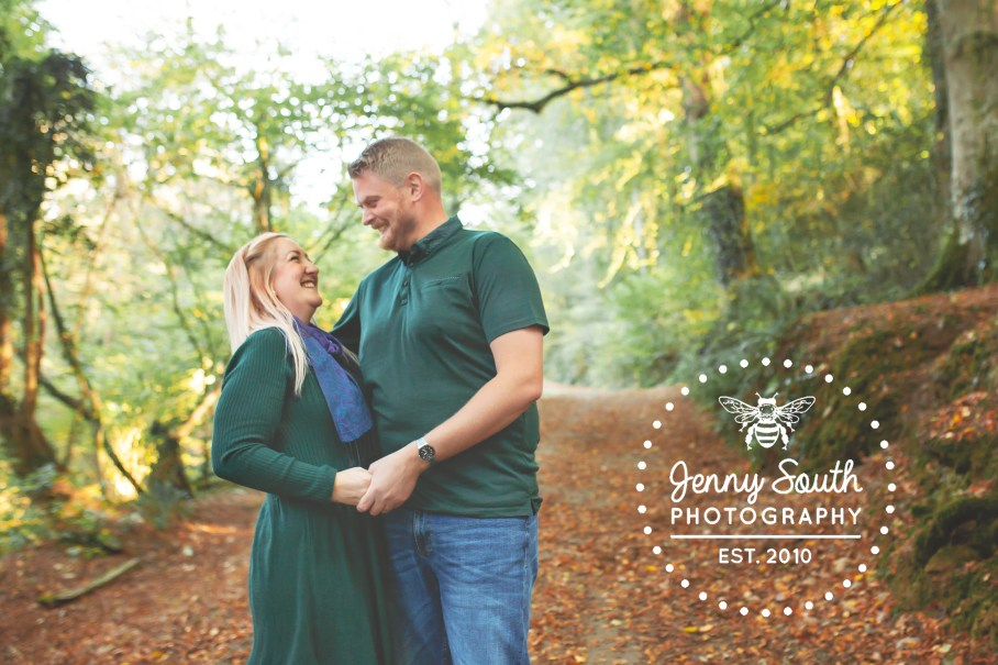 A couple laugh in the autumn woodland during a family photography session in Plymouth