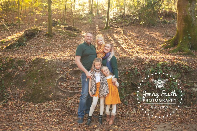 A family pose against a woodland backdrop in the warm autumn sunshine in Plymouths Ham woods