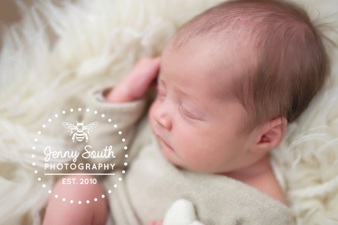 Baby girl sleeps clutching a small felt heart during a newborn photography session