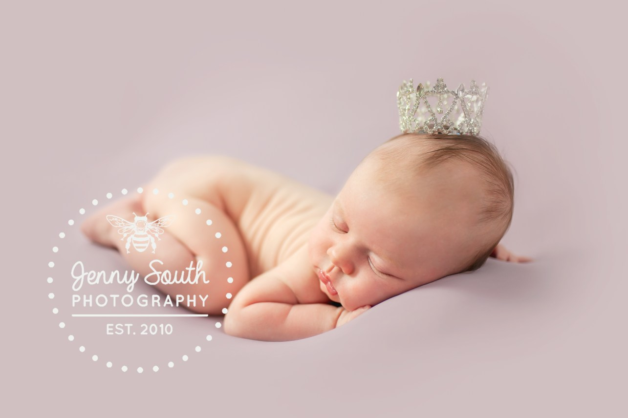 Baby girl sleeps soundly on her tummy with a tiny crown upon her head. against a Violette backdrop