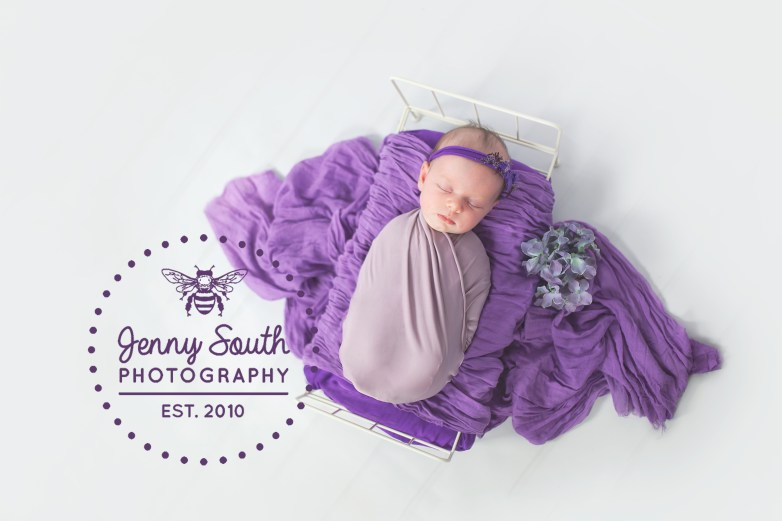 Sleeping beauty. Newborn baby girl sleep onto of a tiny bed surrounded by lushes purple and lilac wraps.