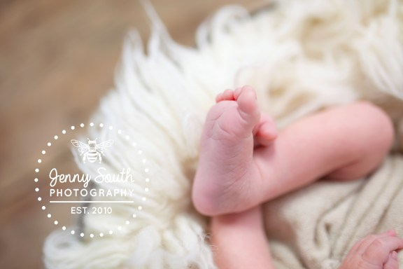 A picture of a newborn babies feet against a white fur background