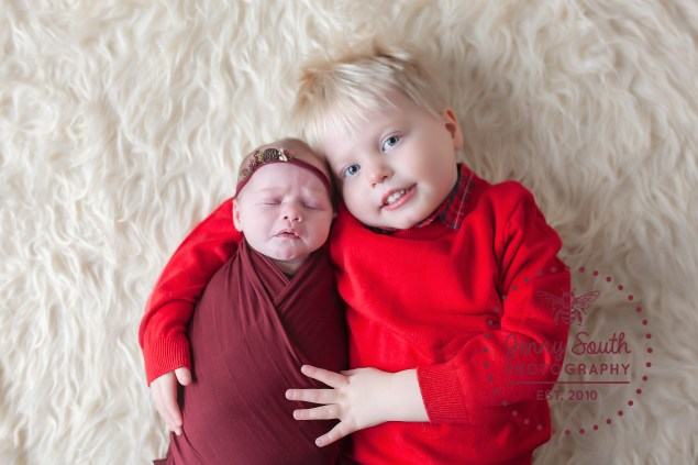 A new big brother cradles his new little sister during a sibling photography