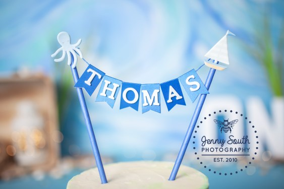 A beautiful handmade cake topper in blue beach hues sits on top of a birthday cake.