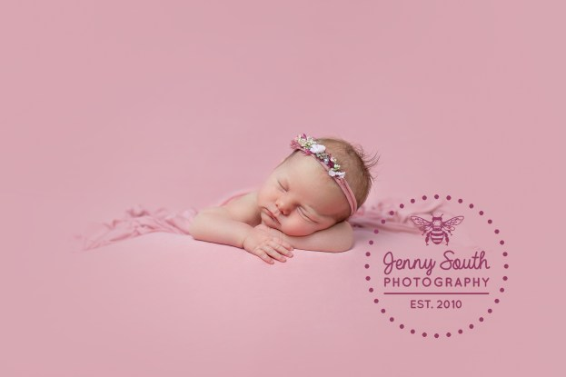 Newborn baby sleeps on her hands on a blanket of blush pink with matching floral headband.