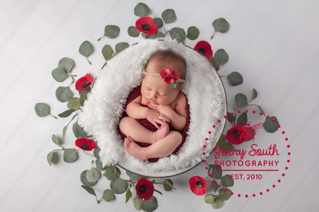 A newborn baby girl lies in the middle of a poppy wreath during her newborn photo shoot