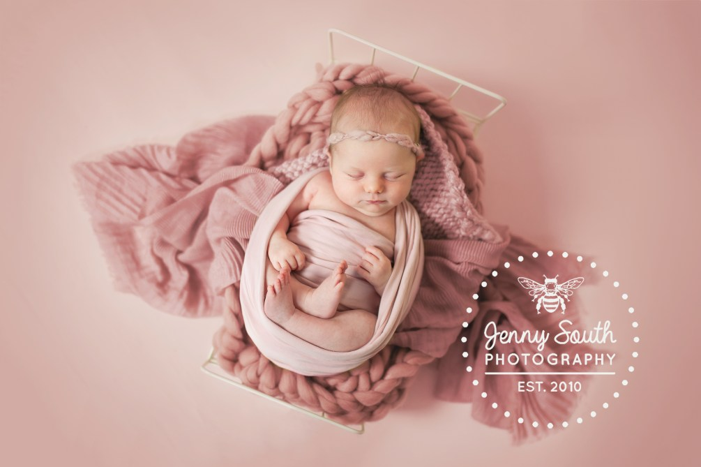 A newborn baby girl sleeps on a bed of many textures.