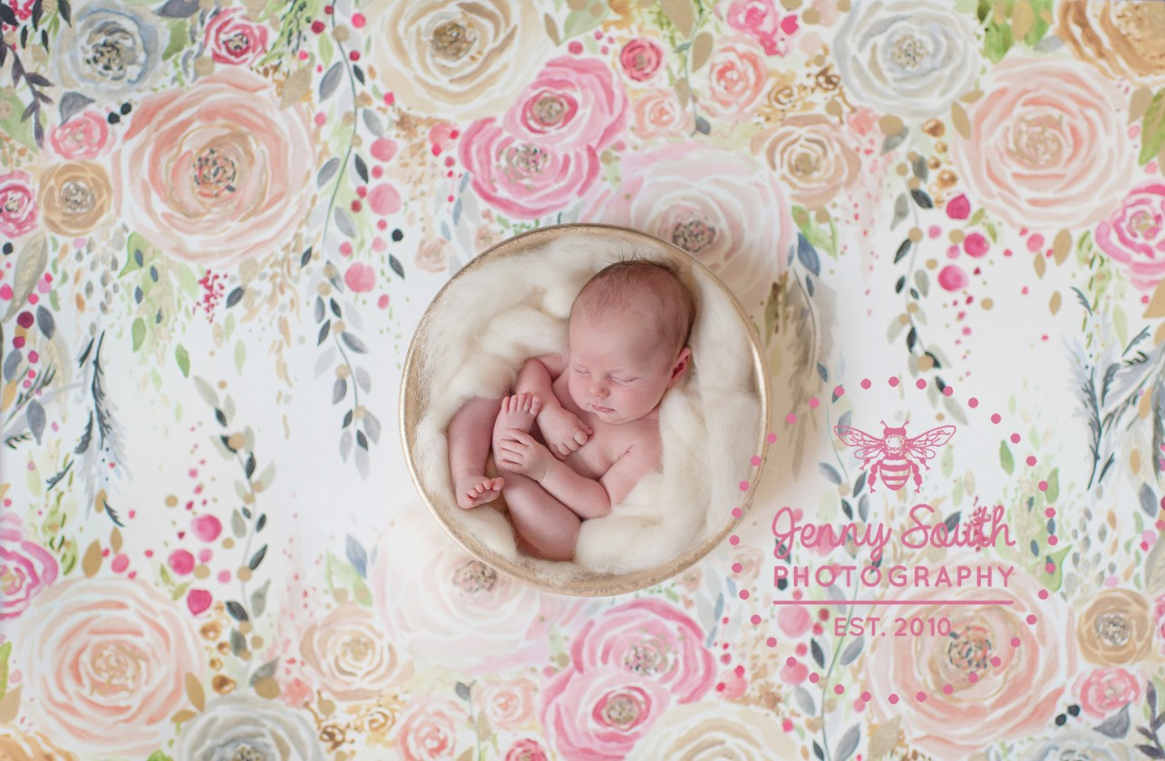 Beautiful sleeping baby is nestled in a wooden bowl against a handprinted watercolour backdrop